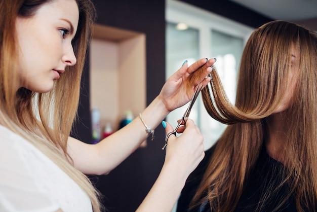 美容院で顔を覆っている長い髪で座っている女性客の枝毛をトリミング