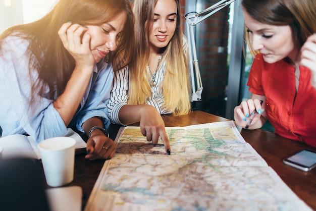 Три подружки планируют свой отпуск, сидя за столом вокруг карты, выбирая пункт назначения