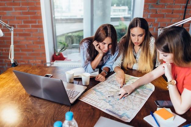 Офисные работницы планируют отпуск, используя карту