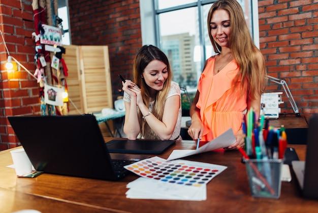 カラーチャートを使用して新しいデザインの色を選択する彼女のオフィスで顧客と働く創造的な女性インテリアデザイナー
