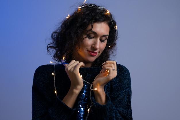 クリスマス白熱灯のお祝いを持つ若い女性。