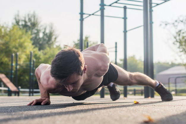 夏に上半身の筋肉を屋外で片腕の腕立て伏せ運動を行うアスリートの若い男性。