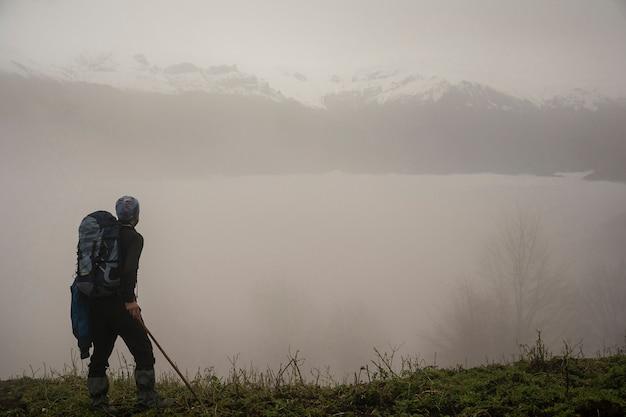 霧の山の丘とフォアグラウンドでバックパックのアクティブハイカー