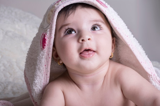 白いバスタオルを着ている小さな赤ちゃんの肖像画を間近します。