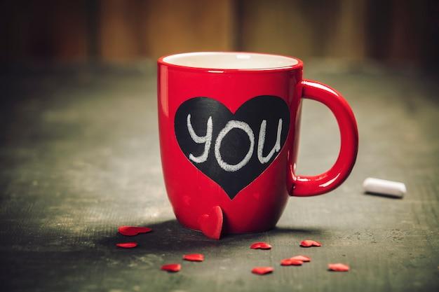 Подарочная коробка дня валентинки красные чашки на деревянной предпосылке.