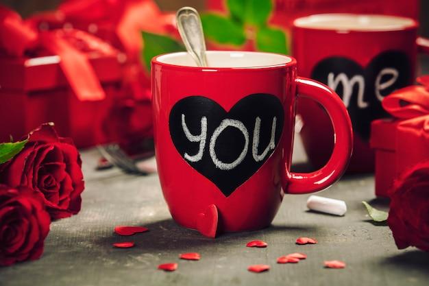 Подарочная коробка дня валентинки красные чашки и розы на деревянной предпосылке.