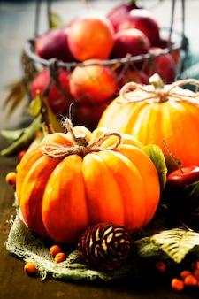 カボチャ、リンゴ、古い木製の背景の葉の秋の静物