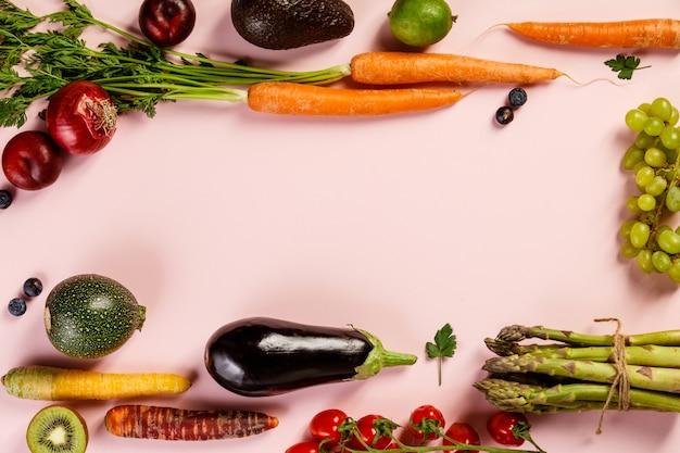 ピンクの背景、フラットレイアウト、トップビューで果物と野菜
