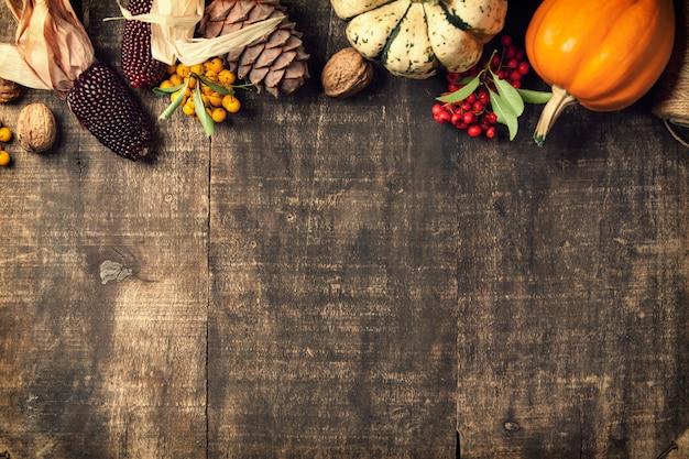 秋の背景-落ち葉と古い木製のテーブルにカボチャ。