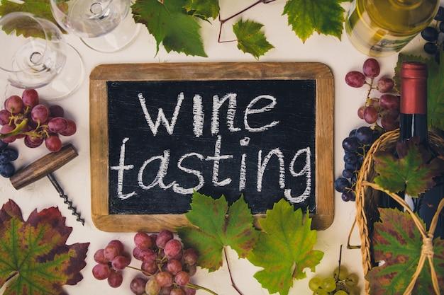 「ワインテイスティング」テキスト付きの黒板。ワイン、ブドウ、ブドウの葉のボトル。上面図