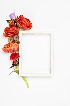 Белая винтажная фоторамка и цветы на белом фоне
