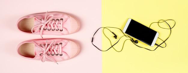 Розовый холст кроссовки и мобильный телефон, крупный план