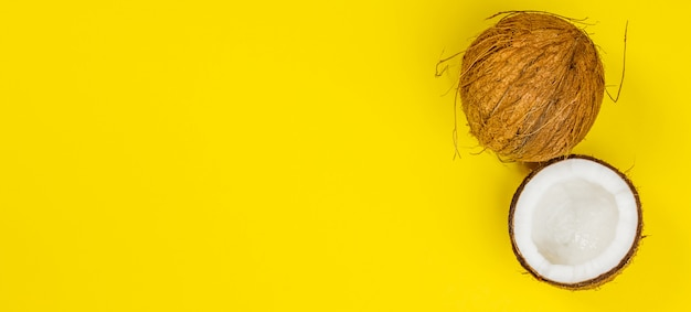 黄色の背景、トップビューでココナッツ