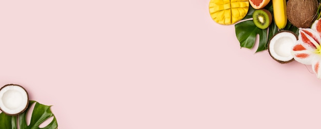 ピンクの背景にトロピカルフルーツと植物の創造的なフラットレイアウト