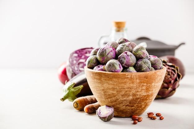 Фиолетовая брюссельская капуста в деревянной миске