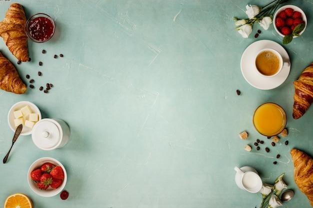 Континентальный завтрак на зеленом фоне стола, вид сверху