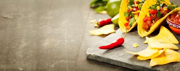 メキシコのナチョスチップとタコス、肉、豆、サルサ添え