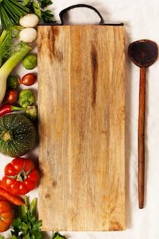 Овощи, травы, специи и пустая разделочная доска