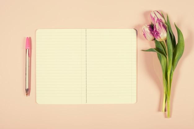 ピンクのチューリップの花束とノートブックを開く