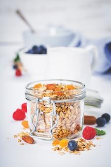 ヘルシーな朝食-自家製グラノーラ、蜂蜜、ミルク、ベリー