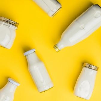 黄色の背景に牛乳の様々なボトル