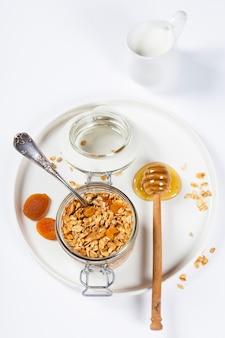 ヘルシーな朝食-自家製グラノーラ、蜂蜜、牛乳