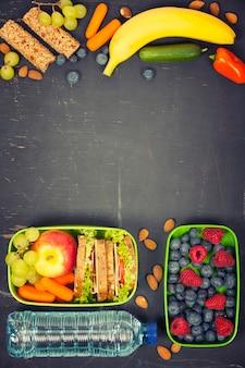 Бутерброд, яблоко, виноград, морковь, ягода в пластиковой коробке и ланч