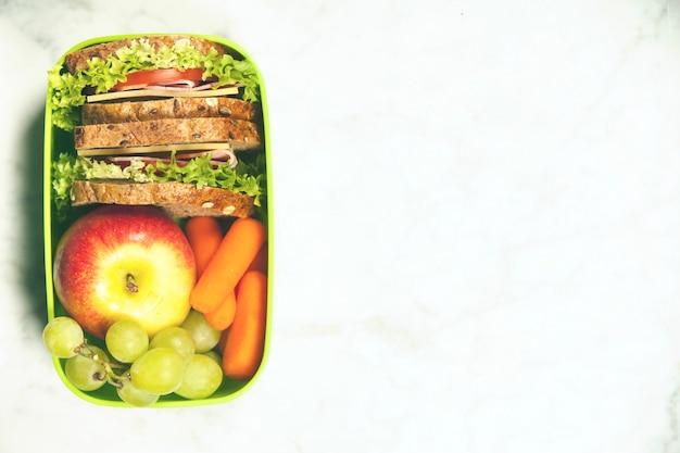 Зеленая коробка школьных обедов с бутербродом, яблоком, виноградом и морковью