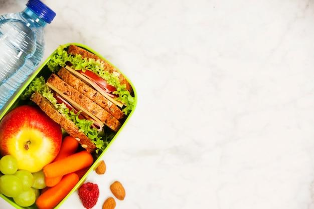 Зеленая коробка школьных обедов с бутербродом, яблоком, виноградом, морковью и б