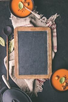 ヴィンテージの黒板の周りのトマトスープと新鮮な食材