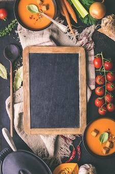 Томатный суп и свежие ингредиенты вокруг классной доски