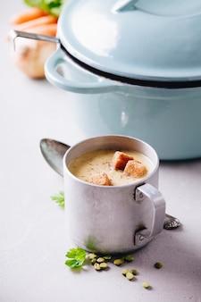 コンクリートの背景にエンドウ豆のスープの古い金属製のカップ