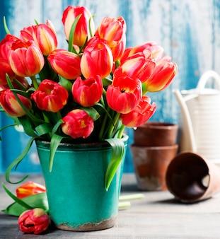 木製のテーブルに美しいチューリップの花束とガーデンツール