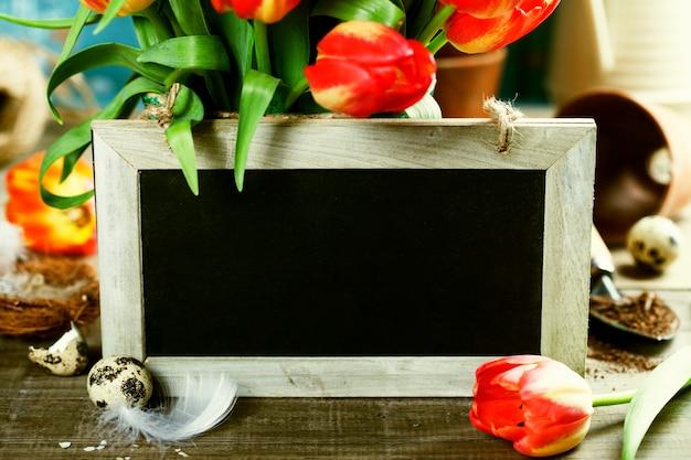 美しいチューリップの花束、イースターエッグ、木製のテーブルのガーデンツール