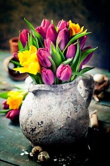 Букет красивых весенних тюльпанов, пасхальные яйца и садовые инструменты