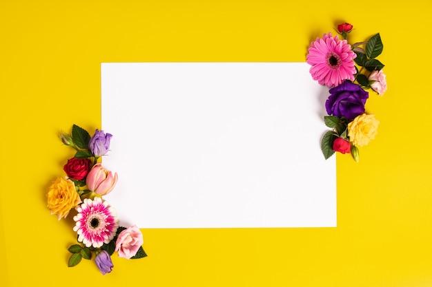 黄色の背景に美しい花で作られた創造的なレイアウト。