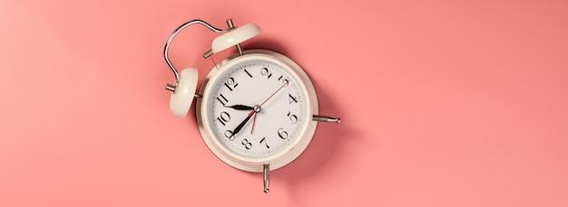 ピンクの背景-パターンに白い目覚まし時計