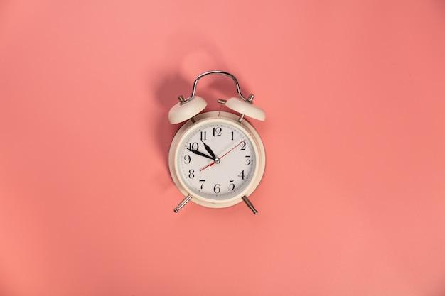 ピンクの背景-フラットに白い目覚まし時計を置く