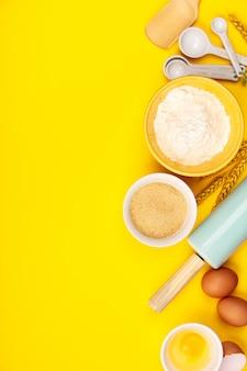 Выпечка или приготовление ингредиентов на желтом фоне, плоская планировка