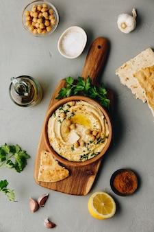 ひよこ豆、赤ピーマン、パセリ、オリーブオイルを添えた自家製フムスの大きなボウル