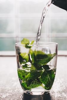 Свежий мятный чай у окна. уютный дом или здоровье