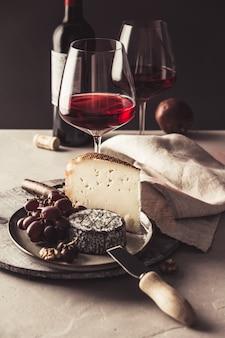 Красное вино и сырная тарелка с фруктами и орехами