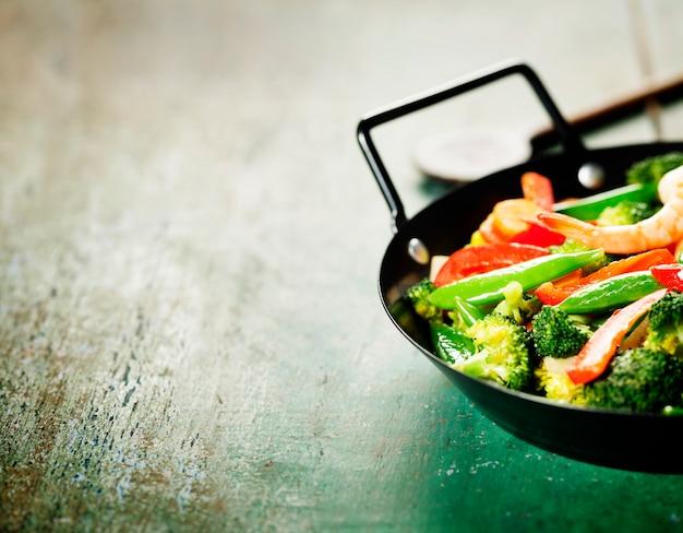 Свежие овощи и креветки на сковороде