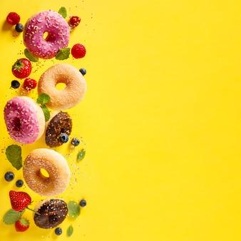 Пончики с окропляет и ягоды в движении, падающие на желтом фоне
