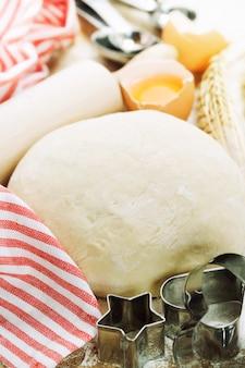 Сырое тесто с инструментами для выпечки