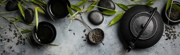 Бамбуковые ветви и зеленый чай на бетонном фоне