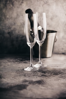 Бутылка шампанского в ведре со льдом и бокалами