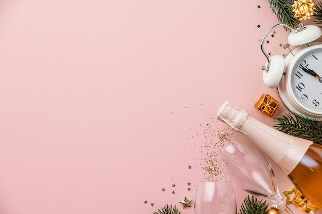 レトロな目覚まし時計、シャンパン、グラス、クリスマスの装飾のボトルとピンクの背景にクリスマスや新年の組成