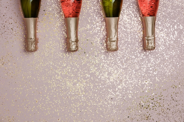 ゴールドラメ、紙吹雪、ピンクの背景上のテキストのためのスペースとシャンパンのボトル