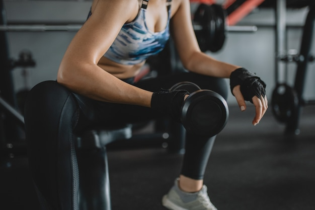 Снятый азиатских женщин поднимая гантели на спортзале, девушка тренировки
